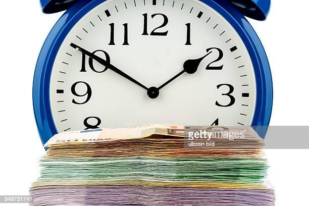 Ein Wecker und Geldscheine Symbolfoto für Lohnkosten Arbeitskosten Zeitarbeit