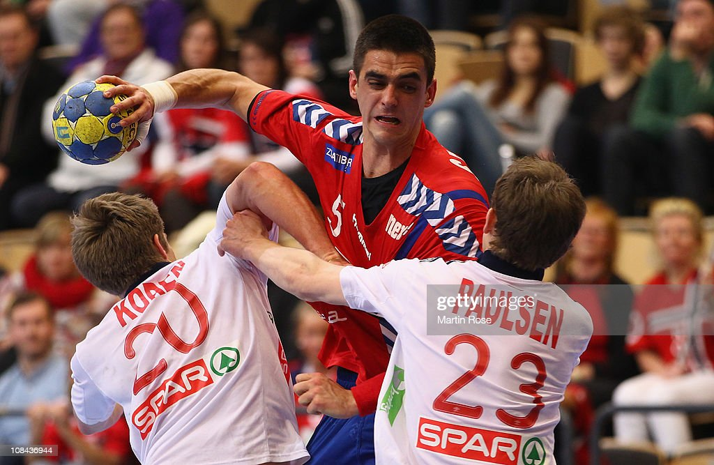 Einar Koren (L) and Sondre Paulsen (R) of Norway are challenged by Zarko Sesum (C) of Serbia during the Men's Handball World Championship placement match between Norway and Serbia at Kristianstad Arena on January 27, 2011 in Kristianstad, Sweden.