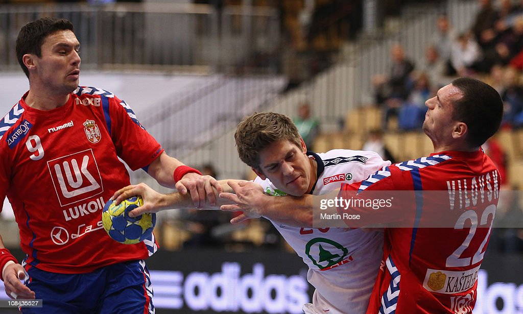 Einar Koren (C) of Norway is challenged by Uros Vilovski (R) and Danimir Curkovic (L) of Serbia during the Men's Handball World Championship placement match between Norway and Serbia at Kristianstad Arena on January 27, 2011 in Kristianstad, Sweden.