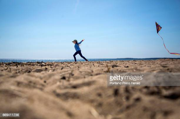 Einda Smith of Phillips trails a kite as she runs along the beach in Old Orchard Beach on Friday April 14 2017 Her grandmother suprised her with the...
