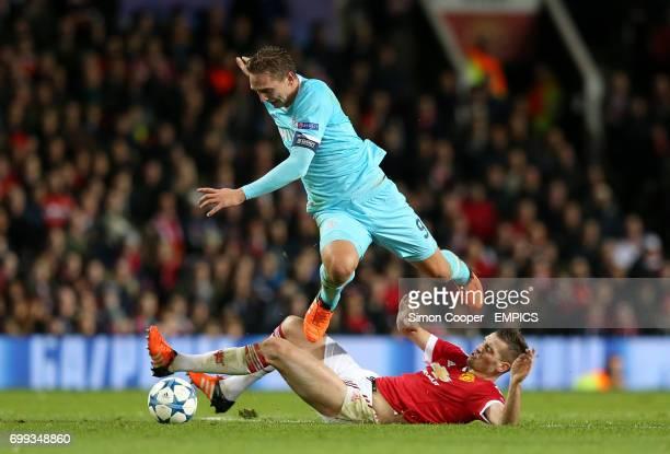 PSV Eindhoven's Luuk de Jong hurdles a challenge from Manchester United's Morgan Schneiderlin