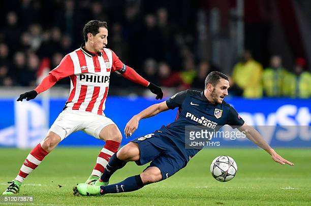 PSV Eindhoven's Mexican midfielder Andres Guardado and Atletico Madrid's midfielder Koke fights for the ball during the UEFA Champions League round...