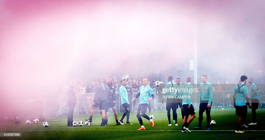 PSV Eindhoven's supporters light firework as PSV Eindhoven's players take part in their first training session of the Eredivisie on June 27, 2016 in Eindhoven. / AFP / ANP / Jerry Lampen / Netherlands OUT