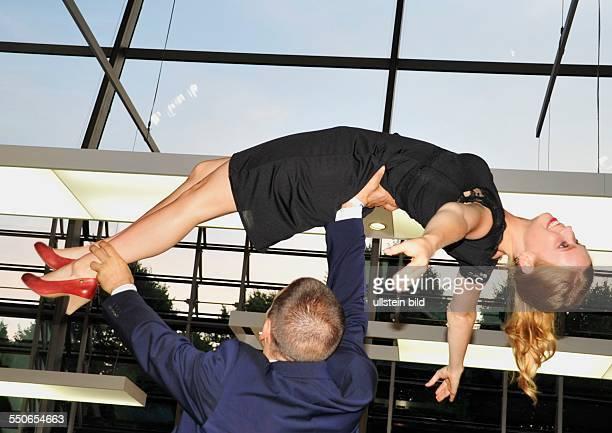 Eine Frau auf Händen tragen Performance beim Bayerischen Sportpreis in der BMW Welt in München