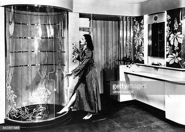 eine Frau in einem gut ausgestatteten Badezimmer Duschkabine aus Plexiglas die Wassersprüher sind in vier Reihen an der Kabinenwand angebracht 1955