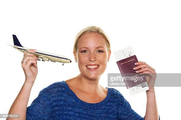 Eine Frau mit dem Modell eines Flugzeuges freut sich auf Ihre nächste Flugreise Mit Flugticket und Reisepass