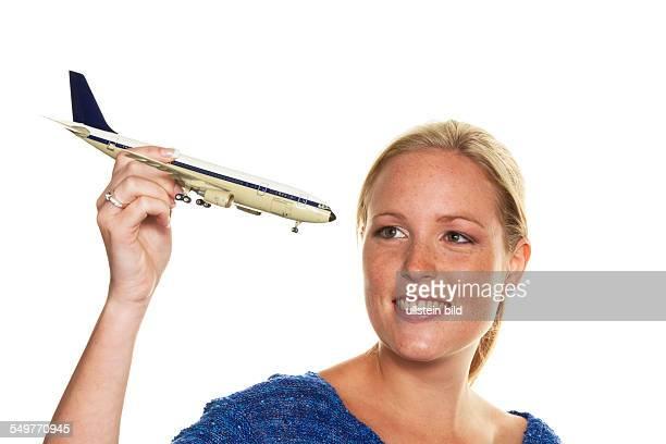 Eine Frau mit dem Modell eines Flugzeuges freut sich auf Ihre nächste Urlaubsreise