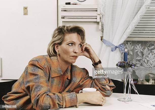 Eine Frau sitzt mit nachdenklichem Gesichtsausdruck und auf die Hand gestütztem Kopf am Tisch Sie trägt Goldschmuck an Armen Fingern und Ohren Vor...