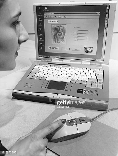 Eine Frau sitzt vor einem Notebook und hat ihren Zeigefinger an der Computermaus Auf dem Laptop ist das Zugangssicherungssystem 'Fingertip' von...