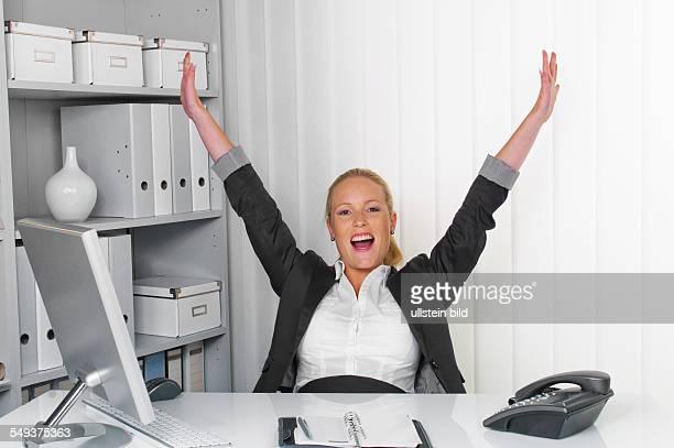 Eine junge erfolgreiche Frau sitzt an ihrem Schreibtisch im Büro