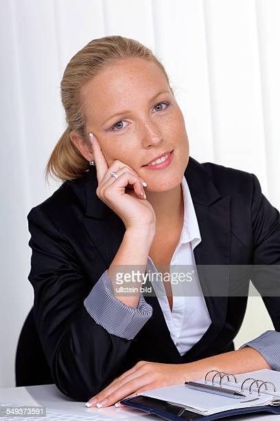 Eine junge erfolgreiche Geschäftsfrau sitzt an ihrem Schreibtisch im Büro