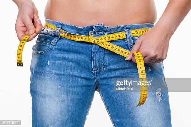 Eine junge Frau mit einem Maßband vor der nächsten Diät Abnehmen und fasten