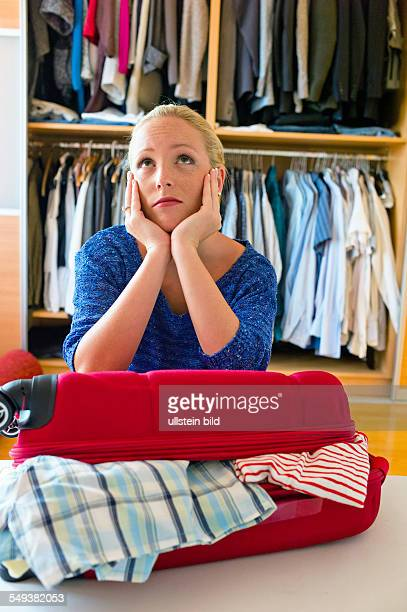Eine junge Frau packt ihren Koffer für die Reise in den Urlaub