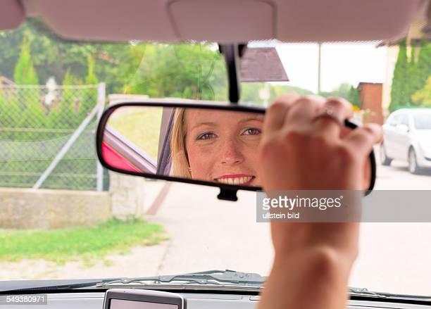 Eine junge Frau richtet vor der Fahrt den Rückspiegel in ihrem neuen Auto