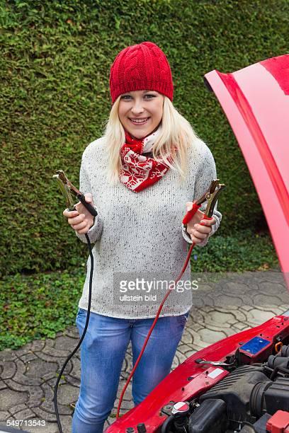 Eine junge Frau startet ihr Auto mit Starterkabel Starthilfe im Winter an kalten Tagen