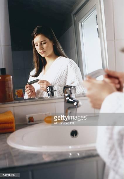 Eine junge Frau steht im Badezimmer vor dem Spiegel und hält eine Packung mit AntiBabyPillen in der Hand Undatiertes Foto