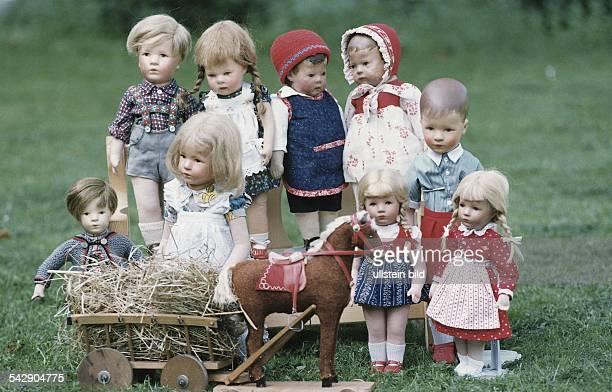 Eine Sammlung verschiedener KätheKrusePuppen ist auf einem Rasen zusammen mit einem Spielzeugpferd samt Heuwagen ausgestellt Die Puppen stammen aus...