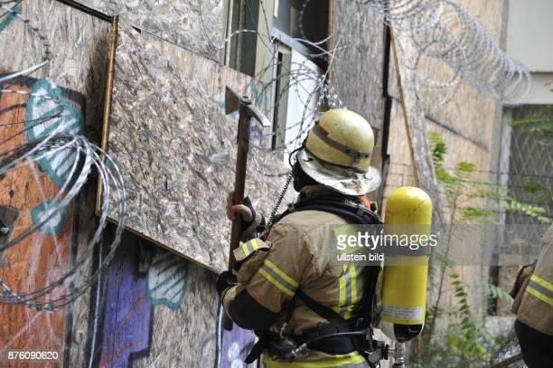 Einsatzkräfte verschaffen sich Zugang zu einem leerstehenden Gebäude in dem ein Brand vermutet wird