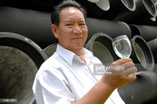 Ek Sonn Chan general director of the Phnom Penh Water Supply Authority with a glass of drinkable water produced at the purification unit