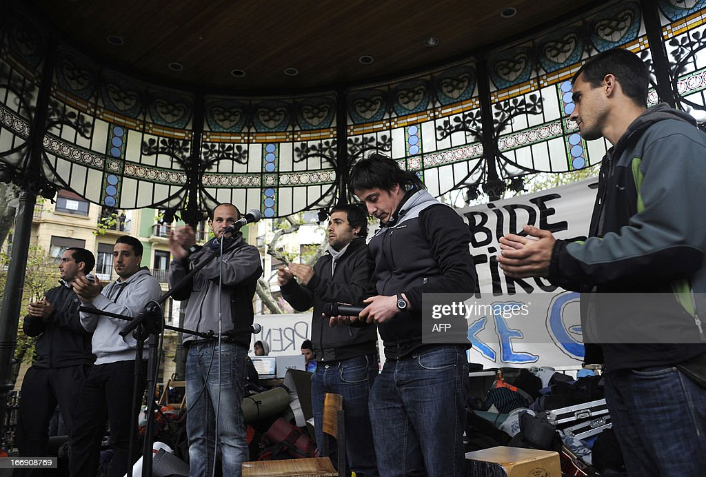 Ekaitz Ezkerra, Mikel Arretxe, Aitor Olaizola, Egoi Alberdi, Adur Fernandez applaud Oier Lorente (2nd R) after he delivered a speech at the 'Askegunea' (Free Zone) in the northern Spanish Basque city of San Sebastian on April 18, 2013. Hundreds of people remain gathered in San Sebastian, to prevent the incarceration of eight members of SEGI sentenced to six years in prison by the Supreme Court. The Spanish Court issued arrest warrants on April 16 against Mikel Arretxe, Imanol Vicente, Naikari Otaegi, Egoi Alberdi, Aitor Olaizola, Adur Fernandez, Oier Lorente y Ekaitz Ezkerra for membership in an organized armed group. AFP PHOTO / ANDER GILLENEA