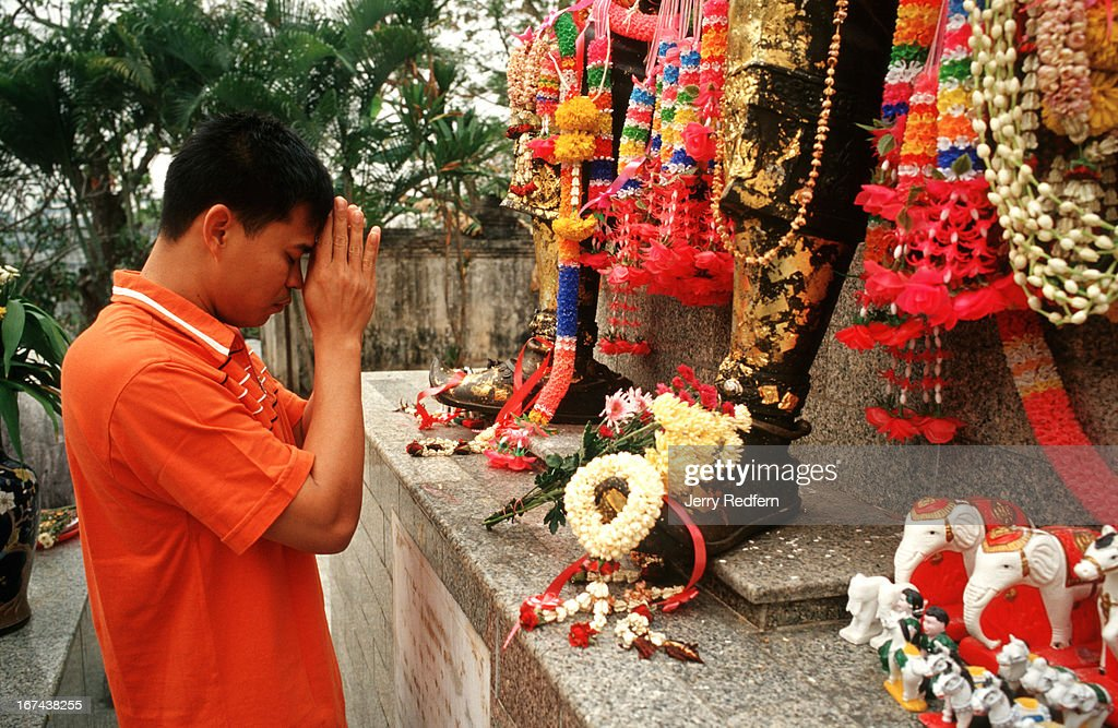 Ekarat from Mae Sai town prays to an image of King Mengrai at Wat Ngam Muang temple in Chiang Rai..