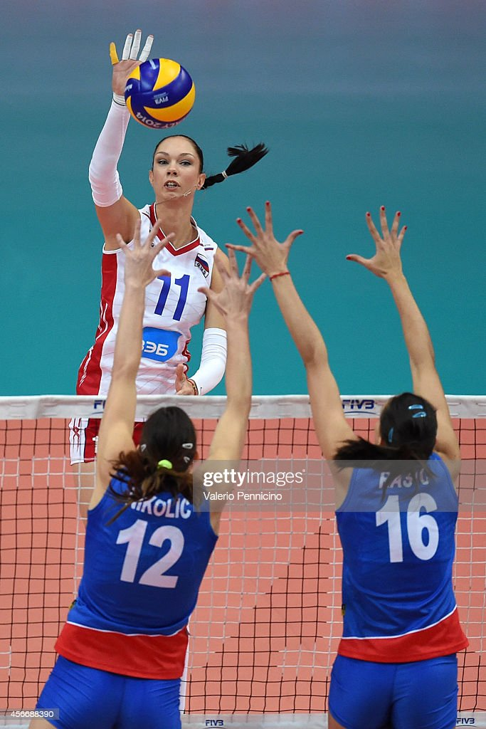 Ekaterina Gamova of Russia spikes as Milena Rasic (R) and <a gi-track='captionPersonalityLinkClicked' href=/galleries/search?phrase=Jelena+Nikolic&family=editorial&specificpeople=704889 ng-click='$event.stopPropagation()'>Jelena Nikolic</a> (L) of Serbia block during the FIVB Women's World Championship pool F match between Serbia v Russia on October 5, 2014 in Verona, .