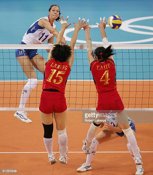 Ekaterina Gamova of Russia spikes the ball past Lina Wang and Yanan Liu of China in the women's indoor Volleyball gold medal match on August 28 2004...