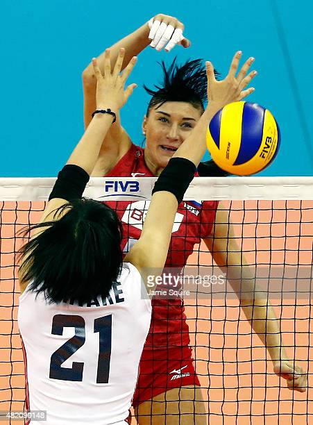 Ekaterina Lyubushkina spikes the ball as Riho Otake of Japan defends during day 5 of the FIVB Volleyball World Grand Prix on July 26 2015 in Omaha...