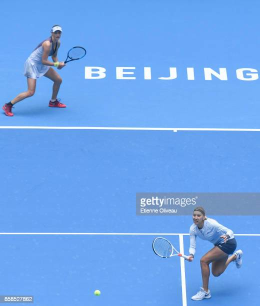 Ekaterina Makarova and Elena Vesnina of Russia return a shot against Timea Babos of Hungary and Andrea Hlavackova of the Czech Republic during their...