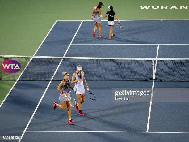 Ekaterina Makarova of Russia and Elena Vesnina of Russia and Zhaoxuan Yang of China and Shuko Aoyama of Japan go to their starting position in their...