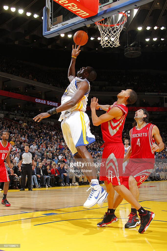 Ekpe Udoh #20 of the Golden State Warriors attempts a reverse layup against Kevin Martin #12 and Luis Scola #4 of the Houston Rockets on December 20, 2010 at Oracle Arena in Oakland, California.