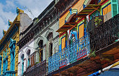 Facades on diagonal. Colorful simple ghetto balcony colonial style. Blue Iron parapet. Blue horse head on the wall.