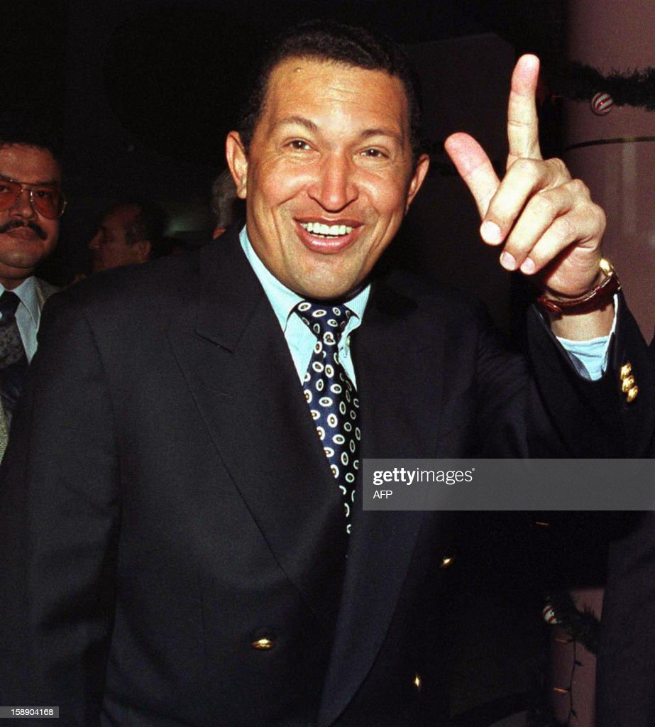 El 'Comandante' Hugo Chavez Frias, ex-golpista, lider del Movimiento V Republica y pre-candidato presidencial, saluda a la prensa despues de amenazar con revisar los contratos con consorcios extrangeros y sancionar a los responsables de haberlos firmado si es elegido presidente, en Caracas, este 15 de Diciembre. AFP PHOTO/BERTRAND PARRES