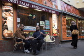 El Mohamed smokes a hookah pipe as he talks with native Palestinian Yaser A Rabah in front of a bar at Sonnenallee in Neukoelln district on October...