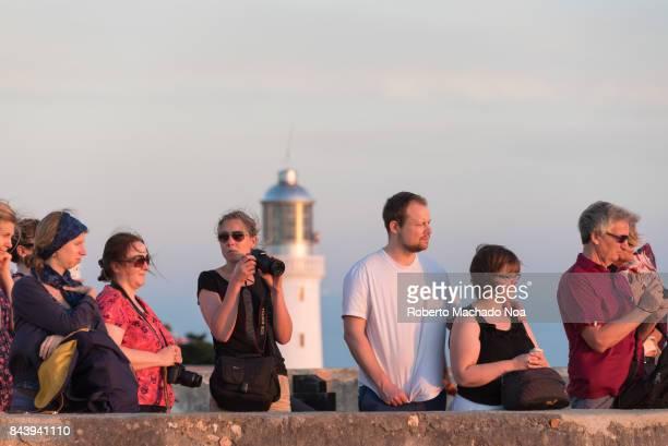 'El Morro de Santiago de Cuba' Tourists standing near a stone ledge of the Unesco World Heritage Site