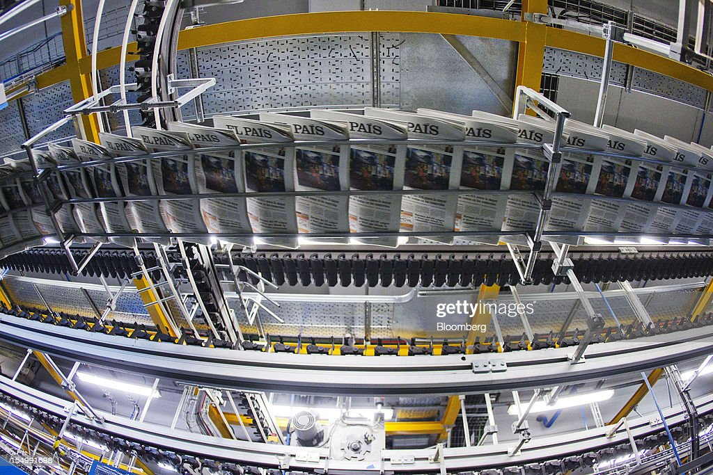 El Pais daily newspapers run through a conveyor after printing at the El Pais printing plant in Madrid, Spain, on Tuesday, Oct. 30, 2012. Prisa, the publisher of El Pais newspaper, has announced staff reductions and salary cuts. Photographer: Angel Navarrete/Bloomberg via Getty Images