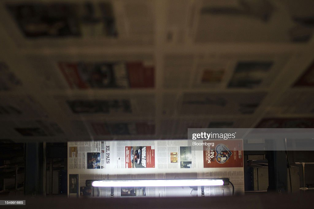 El Pais newspapers run through printing presses at the El Pais printing plant in Madrid, Spain, on Tuesday, Oct. 30, 2012. Prisa, the publisher of El Pais newspaper, has announced staff reductions and salary cuts. Photographer: Angel Navarrete/Bloomberg via Getty Images