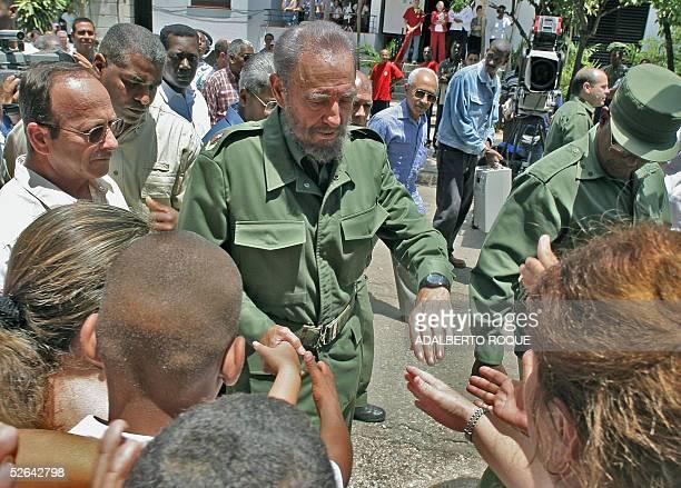 El presidente cubano Fidel Castro saluda a vecinos del Barrio El Vedado en La Habana el 17 de abril de 2005 tras votar para elegir delegados a...