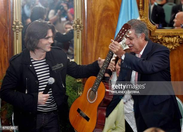 El presidente de Guatemala Oscar Berger le pasa una guitarra al colombiano Juanes para que cante la 'Camisa Negra' en la Sede del Ejecutivo en Ciudad...