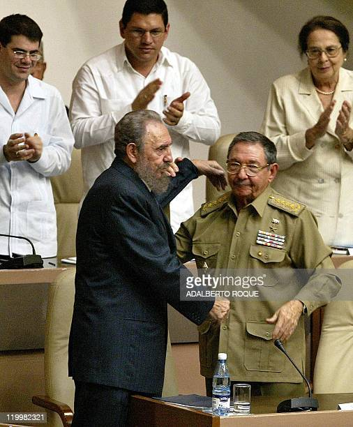 El primer vicepresidente de Cuba y ministro de las Fuerzas Armadas cubanas general Raúl Castro trata de levantar los brazos de su hermano Fidel...