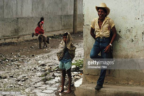 El Salvador, Anamoros Village, boy standing with father in street