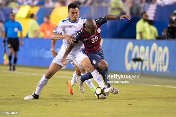 El Salvador Midfielder Darwin Cerén makes a tackle on United States Midfielder Darlington Nagbe in the second half during the CONCACAF Gold Cup...