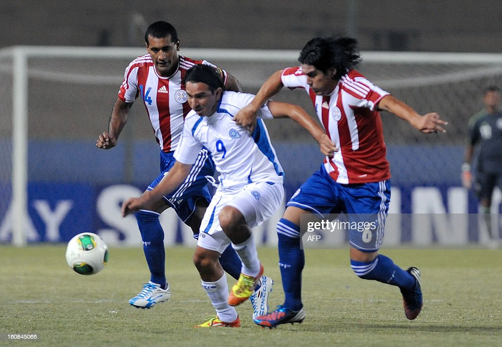El Salvador 's Rafael Burgos ( L) vies for the ball with Paraguay's Fidencio Oviedo during their friendly football match at Nicolas Leoz stadium on February 6, 2013 in Asuncion, Paraguay. AFP PHOTO Gustavo Perina