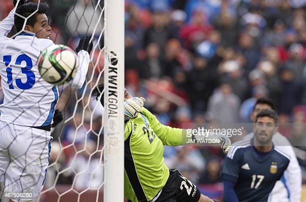 El Salvador's Alexander Larin and goalkeeper Derby Carrillo watch as Federico Mancuello scores a goal during an international friendly match at FEDEX...