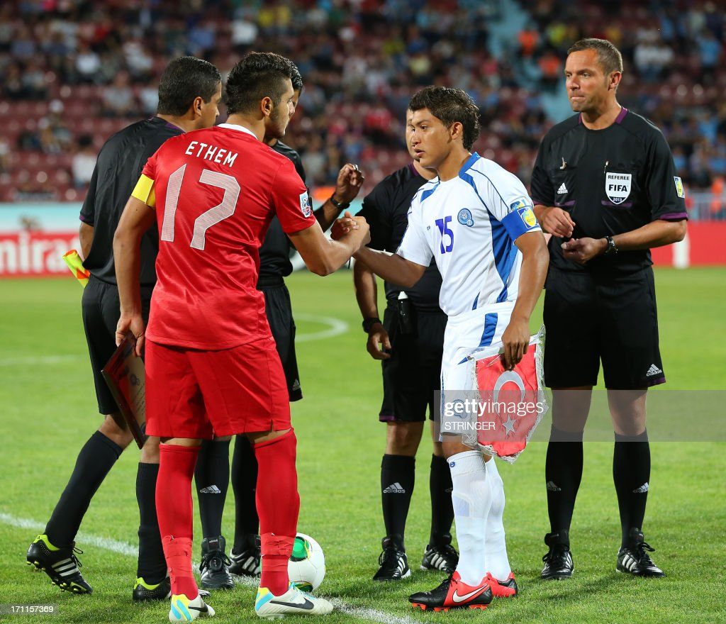 El Salvador's captain Rene Gomez (2nd R) shakes hands with Turkey's captain Ethem Pulgir during the group stage football match between Turkey and El Salvador at the FIFA Under 20 World Cup at the Avni Aker stadium in Trabzon on June 22, 2013. AFP PHOTO / TURKPIX
