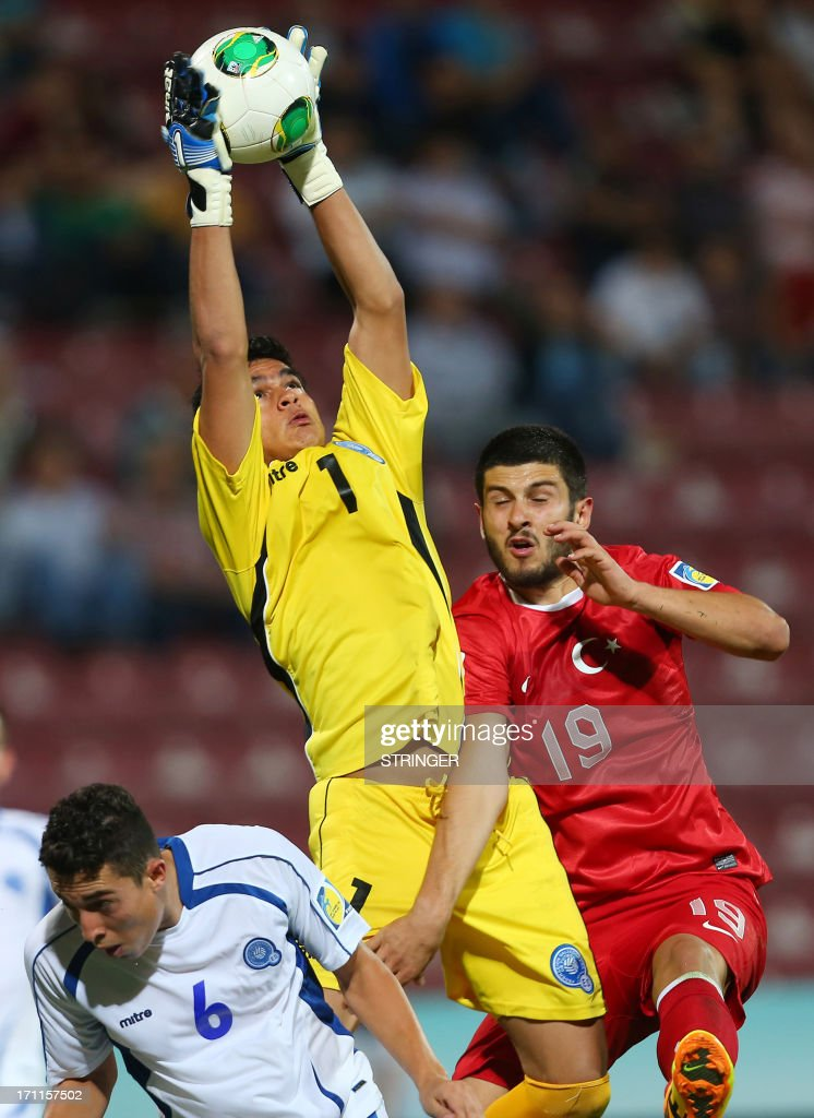 El Salvador's goalkeeper Rolando Morales (C) catches the ball next to El Salvador's Marvin Baumgartner (L) and Turkey's Ibrahim Yilmaz (R) during the group stage football match between Turkey and El Salvador at the FIFA Under 20 World Cup at the Avni Aker stadium in Trabzon on June 22, 2013.