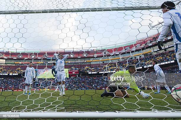 El Salvador's Nestor Renders reacts as Alexander Larin and Goalkeeper Derby Carrillo tend Argentina's Federico Mancuello's goal during an...