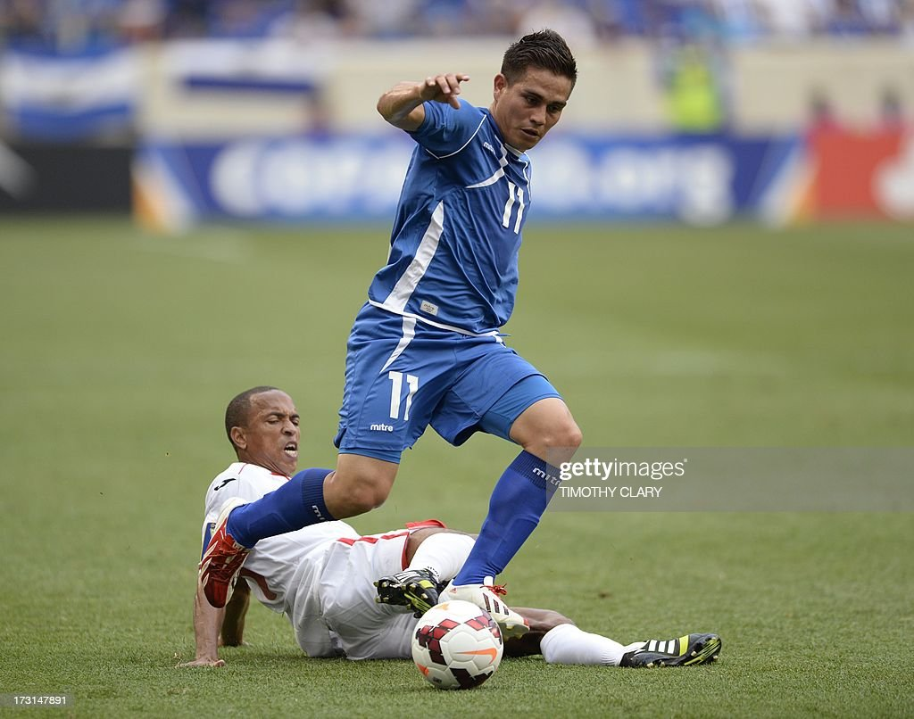 El Salvador's Rodolfo Zelaya escapes with the ball past Trinidad Tobago's Denzil Theobald during their CONCACAF Gold Cup match on July 8 2013 at the...