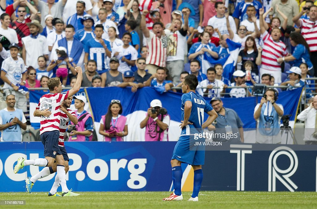 El Salvador's Rodolfo Zelaya Garcia (R) watches as USA's Landon Donovan (C) celebrates with Clarence Goodson (L) after Goodson scored a goal in the first half of a CONCACAF Gold Cup quarterfinal match in Baltimore on July 21, 2013. AFP PHOTO/JIM WATSON