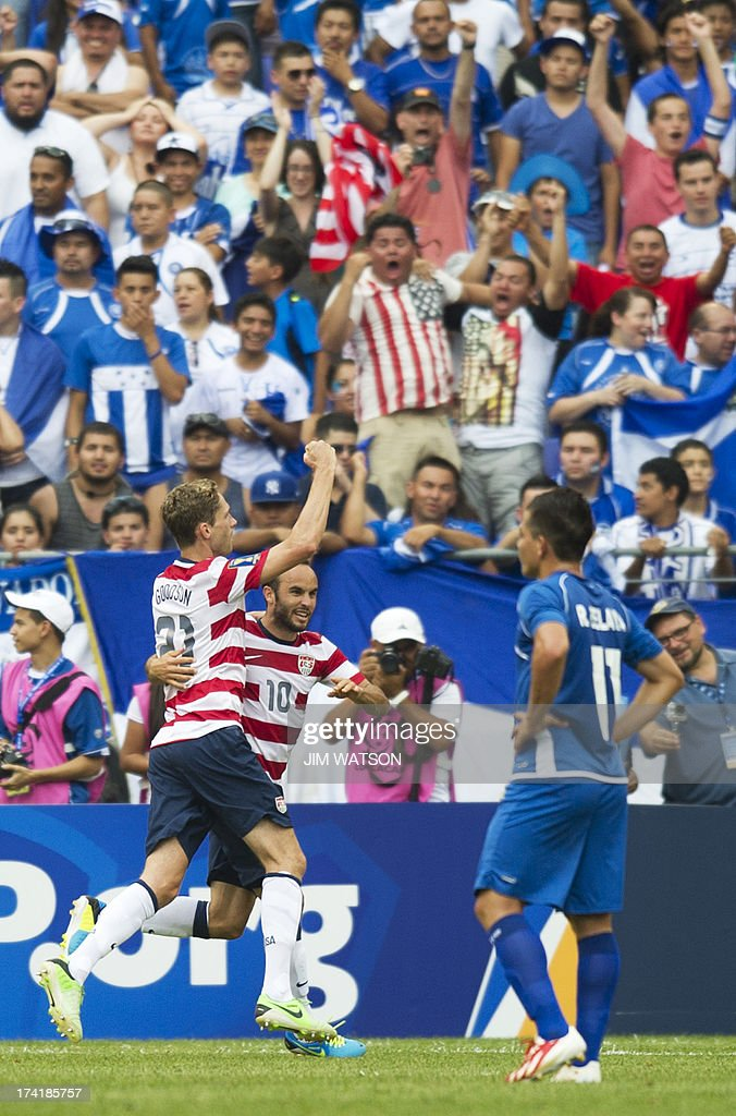 El Salvador's Rodolfo Zelaya Garcia (R) watches as USA's Landon Donovan (C) celebrates with Clarence Goodson (L) after Goodson scored a goal in the first half of a CONCACAF Gold Cup quarterfinal match in Baltimore on July 21, 2013.